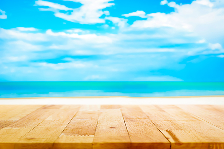 Wood table top on blur white sand beach and blue sky background - can be used for display or montage your products Stock Photo