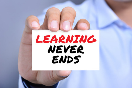 never: LEARNING NEVER ENDS message on the card shown by a man