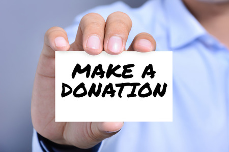 contribution: A man showing card with a message MAKE A DONATION Stock Photo