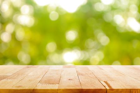 Madera tablero de la mesa en bokeh verde natural resumen de antecedentes - se puede utilizar para el montaje o mostrar sus productos Foto de archivo