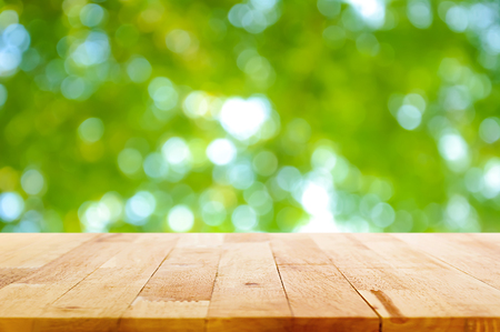 Wood table top on green natural bokeh abstract background - can be used for montage or display your products
