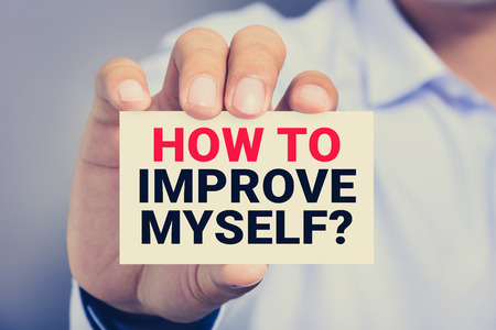 how to: HOW TO IMPROVE YOURSELF? message on the card held by a man hand, vintage tone