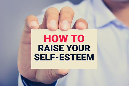 self worth: HOW TO RAISE YOUR SELF-ESTEEM, message on the card shown by a man, vintage tone