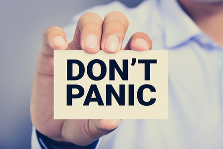 shown: DONT PANIC, message on the card shown by a man