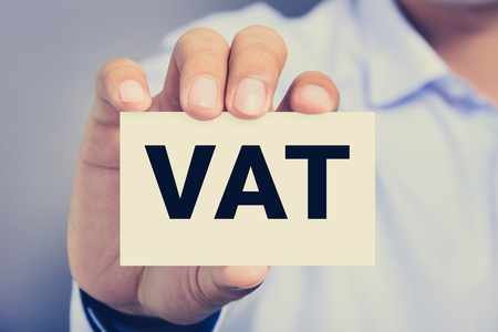 vat: VAT letters (or Value Added Tax) on business card shown by a man