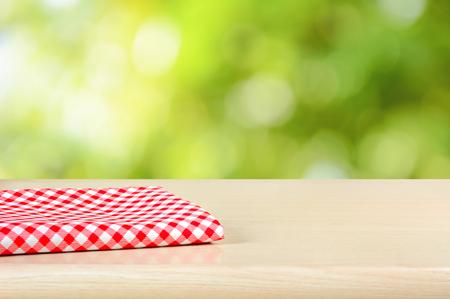 赤緑ボケ抽象的な背景の上の木のテーブルの上に布を格子縞 - 表示に使用することができますまたはあなたのプロダクトをモンタージュ