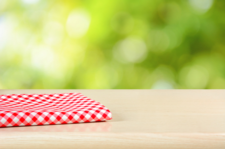 picnic cloth: Red checkered cloth on wood table top in green bokeh abstract background - can be used for display or montage your products