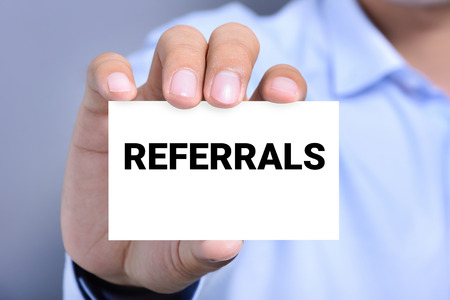 referrals: REFERRALS word on business card shown by a man