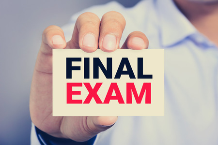 final: FINAL EXAM message on the card shown by a man Stock Photo