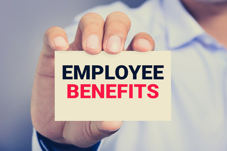 financial reward: EMPLOYEE BENEFITS, message on business card shown by a man, vintage tone Stock Photo