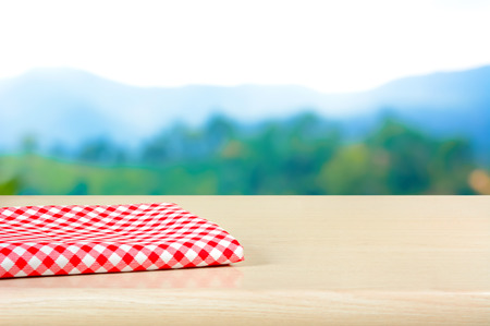 red mountain: Red checkered cloth on wood table top in blur mountain background - can be used for display or montage your products Stock Photo