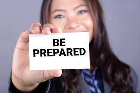 be prepared: BE PREPARED, message on the card shown by a businesswoman