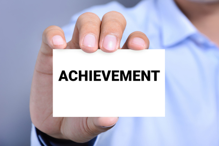 achieve: ACHIEVEMENT word on the card shown by a man Stock Photo
