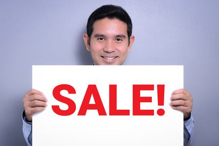 discounted: Smiling man holding SALE! sign