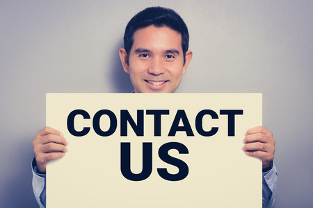 contact us sign: Smiling man showing CONTACT US sign, vintage tone
