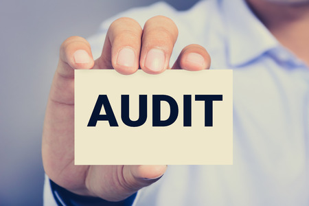 financial audit: AUDIT word on the card card shown by a man Stock Photo