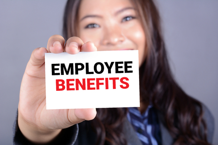care allowance: EMPLOYEE BENEFITS, message on business card shown by a businesswoman Stock Photo
