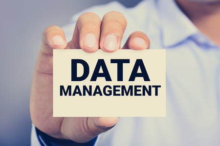 data management: DATA MANAGEMENT, message on business card shown by a man, vintage tone Stock Photo