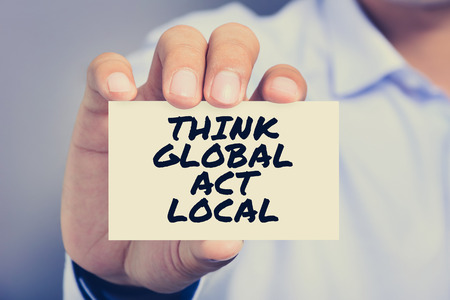 to think: THINK GLOBAL ACT LOCAL message on the card shown by a man, vintage tone