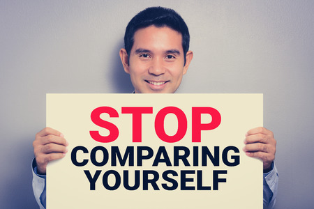 comparing: STOP COMPARING YOURSELF message on white cardboard held by smiling man