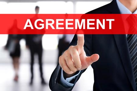 tab: Businessman hand touching AGREEMENT tab on virtual screen