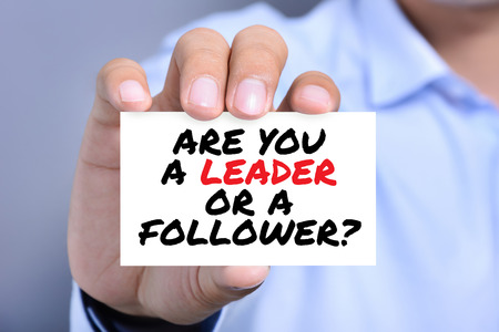 follower: ARE YOU A LEADER OR A FOLLOWER, message on the card held by a man hand Stock Photo