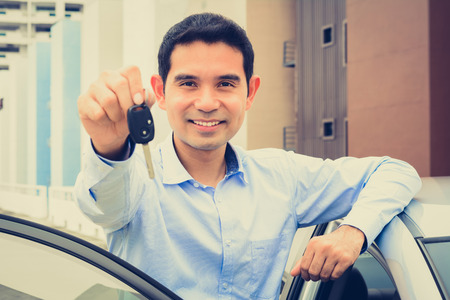 sell car: Smiling Asian man showing car key (face focused), vintage tone
