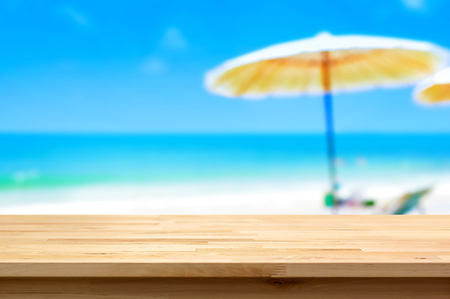 holiday display: Wood table top on blur white sand beach background, summer holiday background concept - can be used for display or montage your products