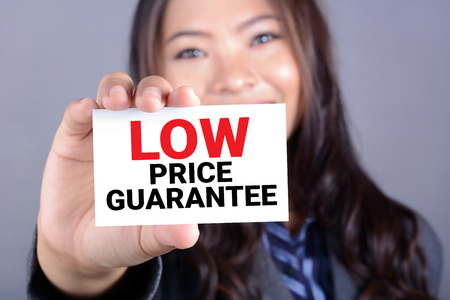 low price: LOW PRICE GUARANTEE message on the card shown by a woman