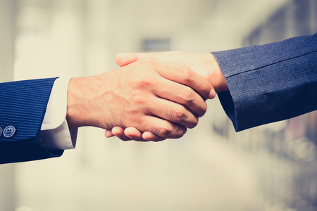 merger: Handshake of businessman and businesswoman,  vintage tone - greeting, dealing, merger and acquisition concepts