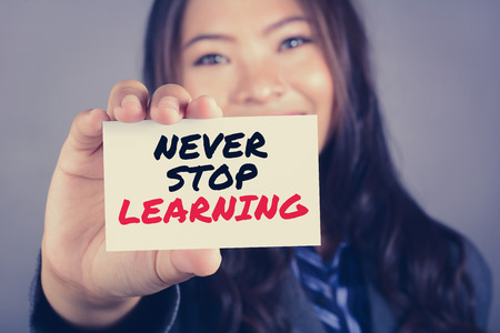 NEVER STOP LEARNING, message on the card shown by a woman, vintage tone 스톡 콘텐츠