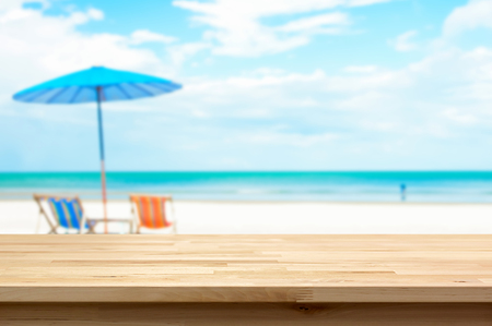 Wood table top on blur white sand beach background, summer holiday background concept - can be used for display or montage your products
