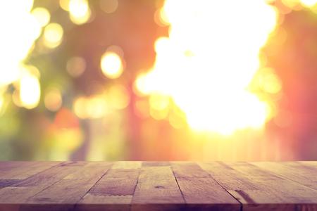 Holztischplatte auf verwischen Hintergrund Sonnenlicht scheint durch die Bäume - kann zur Anzeige oder verwendet montage Ihre Produkte werden
