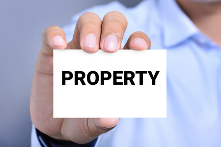 company person: PROPERTY word on the card shown by a man