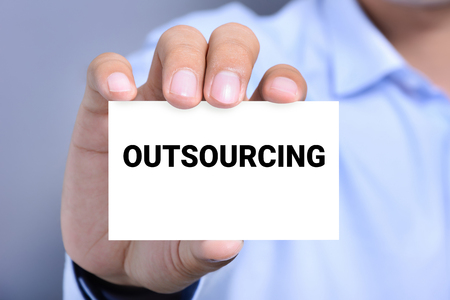 offshoring: OUTSOURCING word on the card shown by a man Stock Photo