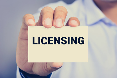 licensing: LICENSING word on the card shown by a man