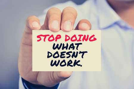 card stop: STOP DOING WHAT DOEST WORK message on the card shown by a man, vintage tone Stock Photo