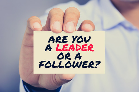 follower: ARE YOU A LEADER OR A FOLLOWER? message on the card held by a man hand, vintage tone