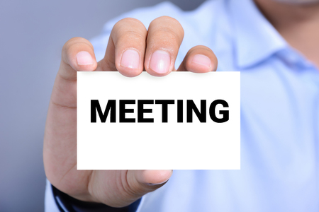 shown: MEETING word on the card shown by a man