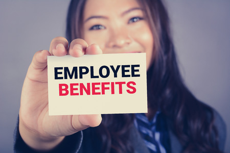 EMPLOYEE BENEFITS, message on the card shown by a businesswoman, vintage tone