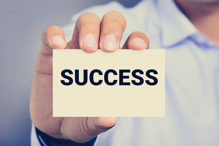 achieve: A man showing card with SUCCESS word, vintage tone Stock Photo