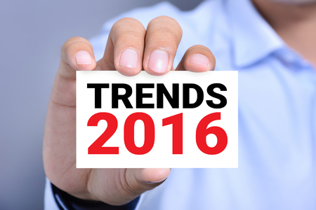 business trends: TRENDS 2016, message on business card held by a man