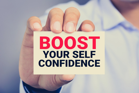 raise your hand: BOOST YOUR SELF CONFIDENCE, message on the card shown by a man, vintage tone Stock Photo
