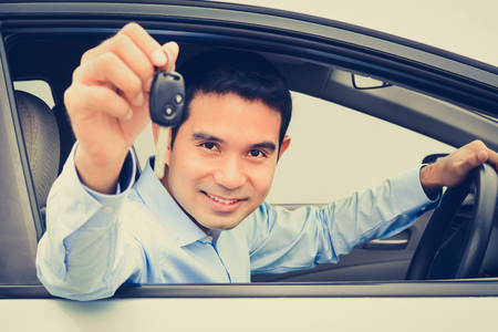 sell: Smiling asian man as a driver showing car key (face focused), vintage tone Stock Photo