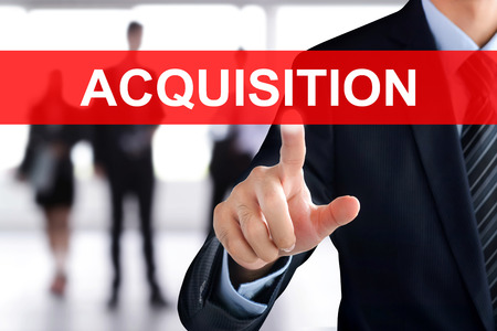 company merger: Businessman hand touching ACQUISITIONS sign on virtual screen Stock Photo