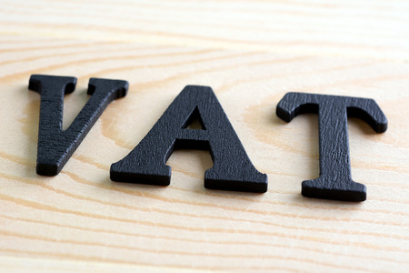 VAT letters (stand for Value Added Tax) on wood background