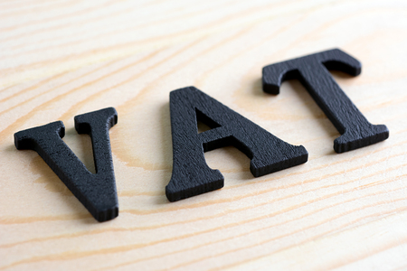 vat: VAT letters (stand for Value Added Tax) on wood background