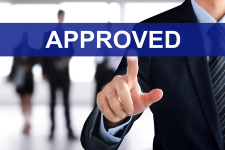 approved sign: Businessman hand touching APPROVED sign on virtual screen