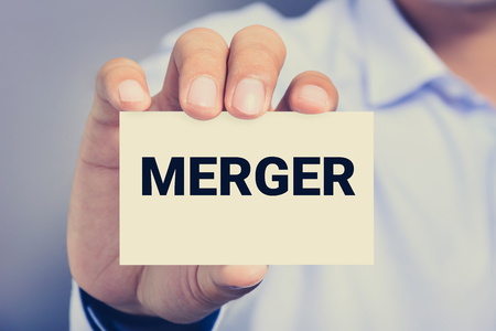 company merger: MERGER word on the card shown by a man, vintage tone