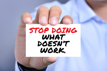 card stop: STOP DOING WHAT DOEST WORK, message on the card shown by a man